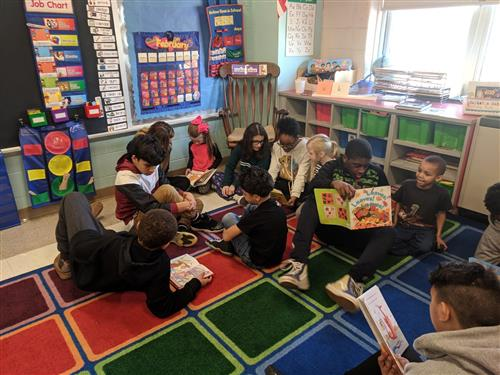 8th graders reading to Kindergarteners